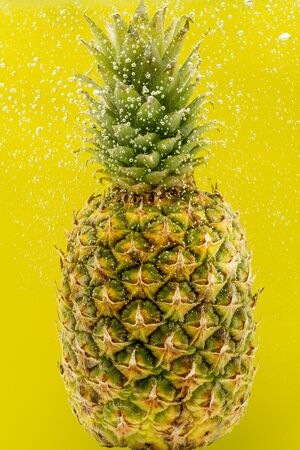 Pineapple under water with bubbles and bubbles on a yellow background