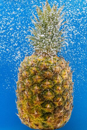 Pineapple under water covered with bubbles and with bubbles in the background blue 版權商用圖片