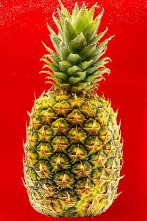 Pineapple under water covered with bubbles on a red background