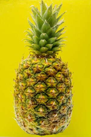 Pineapple under water covered with bubbles on a yellow background