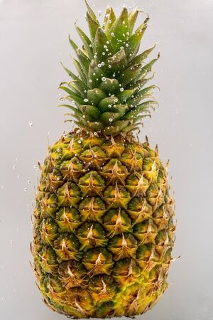 Pineapple under water covered with bubbles and with bubbles in the background white