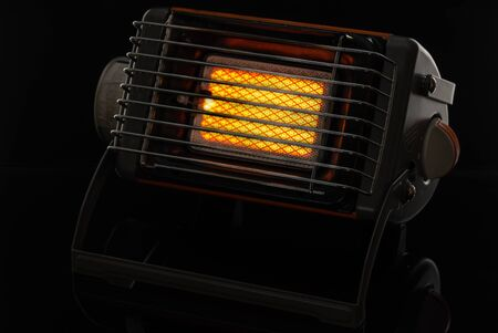 Camping portable gas ceramic heater, works and stands on a black