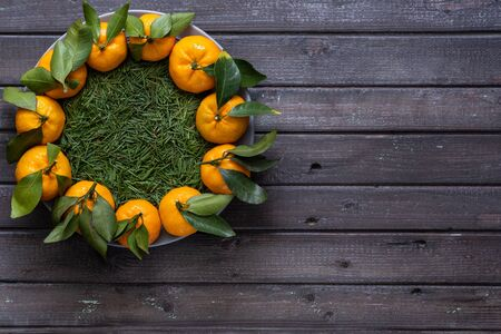 Christmas tangerines with leaves lie in a plate covered with conifer needles