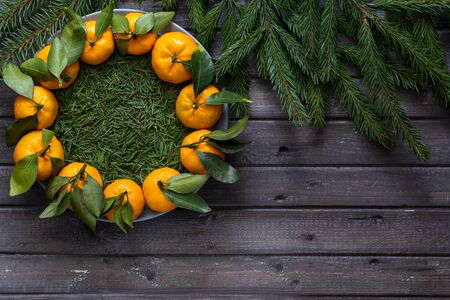 Christmas tangerines with leaves lie in a plate covered with conifer needles on a black wooden table with fir branches Banco de Imagens