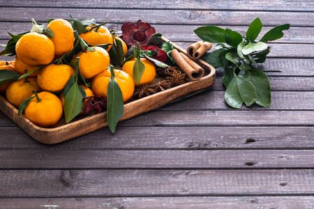 Christmas tangerines with leaves on a wooden tray with spices star anise and cinnamon on a wooden table Banco de Imagens
