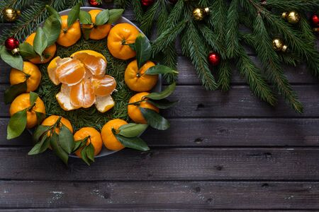 Christmas tangerines with leaves lie in a plate covered with pine needles and with slices of tangerine on a black wooden table wit