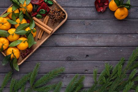 Christmas tangerines with leaves on a wooden tray with spices star anise and cinnamon with fir branches on a wooden table