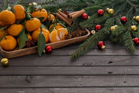 Christmas tangerines with leaves on a wooden tray with spices star anise and cinnamon surrounded by fir branches and Christmas t