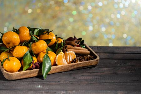 Christmas tangerines with leaves on a wooden tray with spices star anise and cinnamon