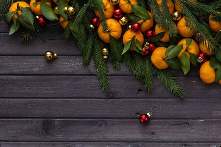 Christmas tangerines with leaves lie in the branches of spruce and Christmas toys on a wooden table
