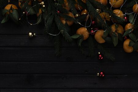 Christmas tangerines with leaves lie in the branches of spruce, garlands and Christmas toys on a wooden table. Top view. Night photo.