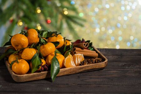 Christmas tangerines with leaves on a wooden tray with spices anise and cinnamon against the background of the New Year tree