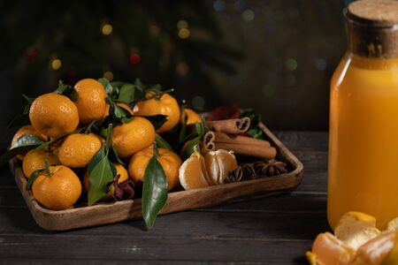 tangerines with leaves on a wooden tray with spices of star anise and cinnamon and tangerine juice on a background of Christmas tree Zdjęcie Seryjne