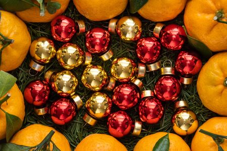 Christmas tangerines with leaves lie in a plate covered with needles of a Christmas tree and Christmas toys close-up