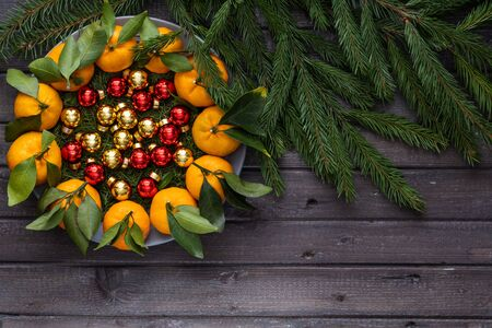 Christmas tangerines with leaves lie in a plate covered with needles of a Christmas tree and Christmas toys