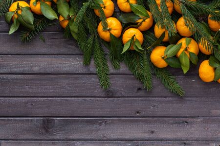 Christmas tangerines with leaves lie in the branches of spruce on a wooden table