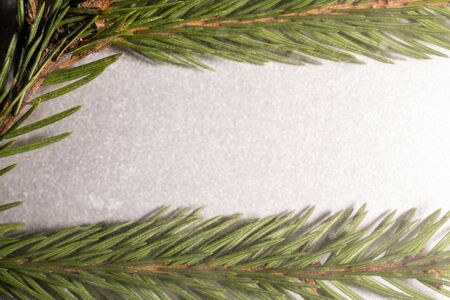 Christmas frame of fir branches on a silver background with the effect of falling snow