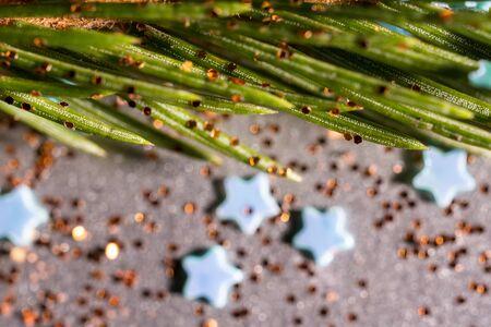 Spruce branch on a silver background and sparkles and confectionery stars Zdjęcie Seryjne