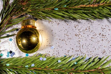 A silver background sprinkled with bright stars and glitter and on which spruce twigs and a Christmas yellow Christmas ball Banco de Imagens