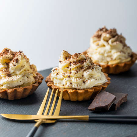 banoffi pie with white cream and chocolate chips, on a stone tray with a fork and knife and chocolate bars