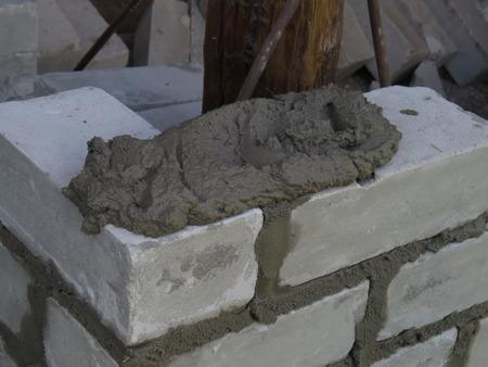 brick mason: Mason builds a wall of white brick.