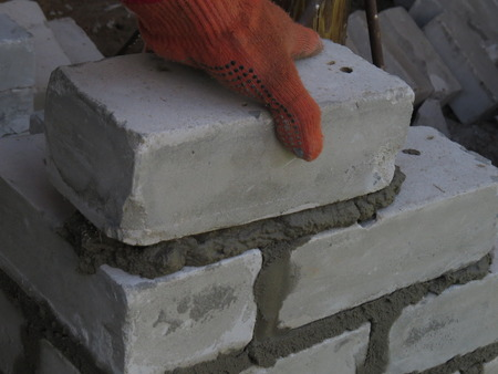 builds: Mason builds a wall of white brick.