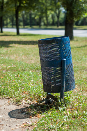 small blue garbage container on a background of green grass