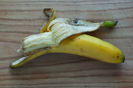 purified: Banana with partially purified peel lies on a wooden surface.