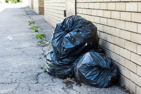 Several black bag of garbage lying on the streets. Stock Photo