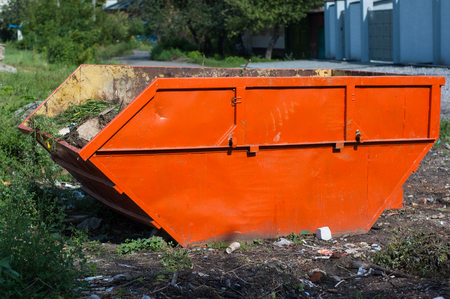 Large orange garbage container standing on the street. Stock Photo