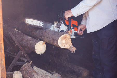 sawing: A man with a chainsaw sawing wood.