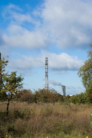Feld im Herbst und Industrie-Schornstein im Hintergrund. Standard-Bild