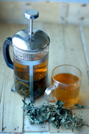 Green herbal tea in a teapot and cup on a wooden background. Stock Photo