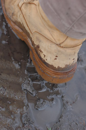 muddy clothes: The foot in the mud close up - big brown terrain boots. Stock Photo
