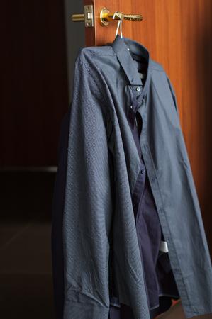 bedroom: A gray shirt hangs on the door handle in the house.