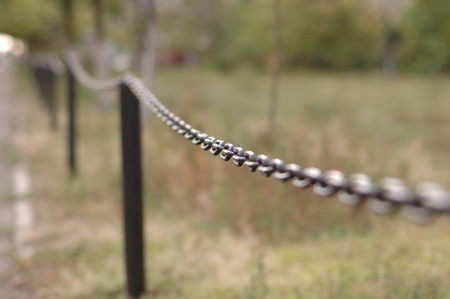 Black metal fence in the garden in the form of a chain.