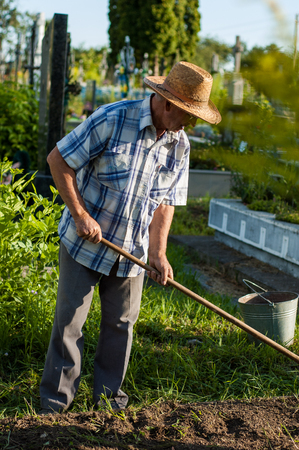 An elderly rural man in a straw hat is working near the grave in the cemetery. Stock Photo