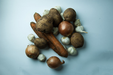 Mixture of vegetables on a white background: potatoes, carrots, garlic, onions. Banque d'images - 96567341