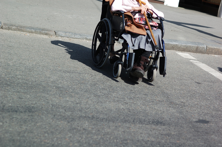 A person in a wheelchair is crossing the road.