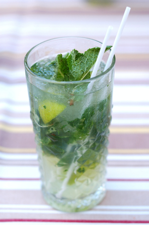 Fresh mojito from mint and lime in a glass on the table.