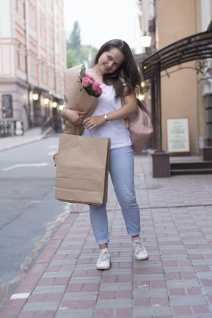 A woman with a bouquet and shopping speaks on the phone in the street.