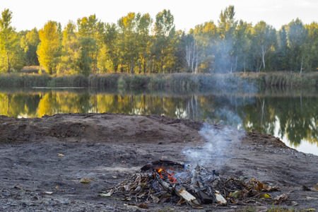 A small fire is burning on the shore of a beautiful lake.