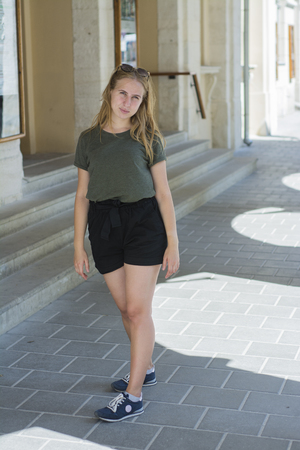 Attractive blonde tourist girl walks through the historic center of the city. Stock fotó