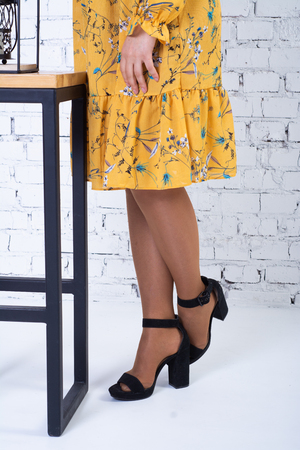 A girl in a bright yellow dress near the bar stool: only the legs and the bottom of the dress are visible.