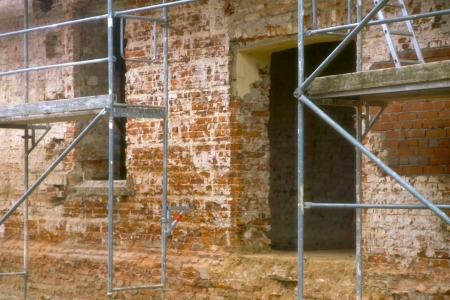 refurbished: building lot - An old house is being refurbished and is provided with a scaffold