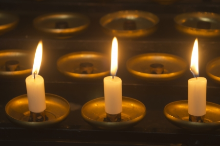 flamme: Three candles - Three burning candles on a dark background   Stock Photo