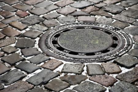 gully: Gully cubrir - Una tapa de alcantarilla en una calle de adoquines en una ciudad antigua en Alemania