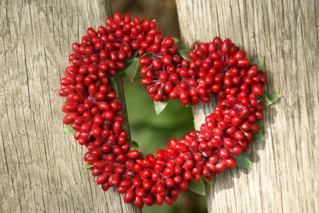 Two wood beams and a red heart made of berries