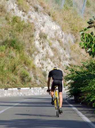 Cycling - A sportsman drives on a street with a bike up a mountain Stock Photo