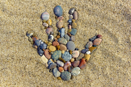 Stone hand - A hand made with little Stones on the beach   Stock Photo